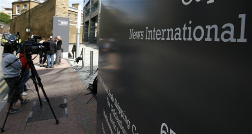 Members of the media gather outside News International's office in London, UK yesterday.