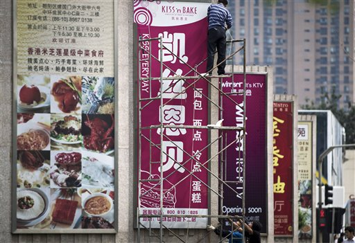 Workers install a bakery's advertisement poster in Beijing, China on June 24.