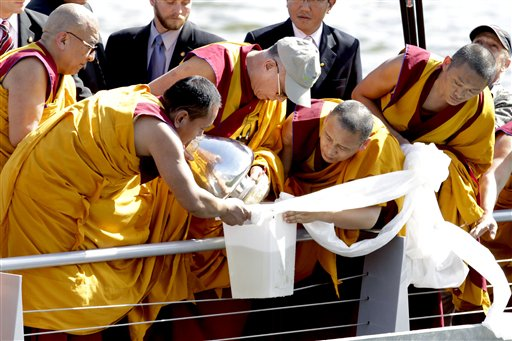 Assisted by monks, the Dalai Lama, center with hat, mixes mandala sand with river water from the Anacostia River as part of a blessing ceremony in Was...
