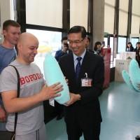 外交部次長曹立傑25日致贈首位抵台俄羅斯旅客外交部台灣造型頸枕(照片來源:外交部提供)