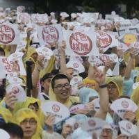 「拒絕紅色媒體、守護台灣民主」活動23日下午在總統府前凱達格蘭大道登場,大批民眾冒雨到場響應,舉出標語表達訴求。
