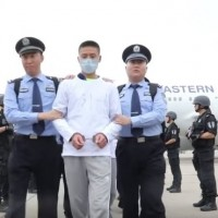 Telecom suspect being escorted to plane (center). (Screenshot from Btime.com)