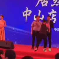 Hong Kong star Simon Yam (on stage, first right) was stabbed by a man (second from right) in the Chinese city of Zhongshan Saturday morning. (screenshot from YouTube)