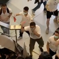 Screenshot showing men in white shirts hitting passengers.
