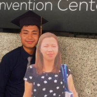 Philippines student holds cardboard cutout of mother at graduation