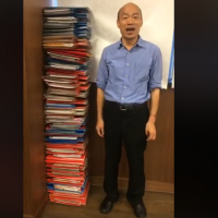 Taiwan's Mayor Han stacks folders high to show off his hard work