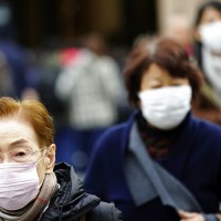 日本16日也傳出武漢肺炎確診個案, 圖為東京街頭戴口罩的民眾 (美聯社)