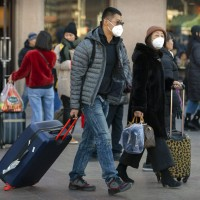 Travelers wear face masks outside Beijing Railway Station, China.