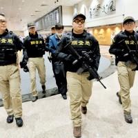楊文虎(中後藍衣者)21日傍晚由美國移民局2名押解官執行遣返,調查局北機站在桃園國際機場接手。中央社