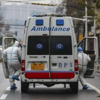 圖為武漢救護車與全副武裝的救護人員(美聯社)