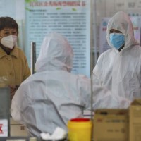 Medical workers in protective gear talk with a woman suspected of being ill with a coronavirus at a community health station in Wuhan.