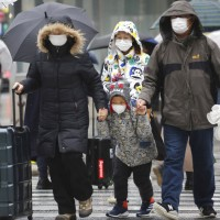 Chinese tourists wear masks at Ginza shopping district in Tokyo, Tuesday, Jan. 28, 2020.