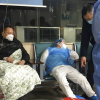 In this Jan. 23, 2020, photo, a medical worker rests in a chair next to a patient at a hospital in Wuhan.