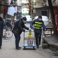 Government workers spray disinfectant along a street in Wuhan in central China's Hubei Province, Tuesday, Jan. 28, 2020.