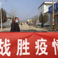 "A man wearing a face mask stands near a banner reading ""defeat the epidemic"" in northern China's Hebei Province, Jan. 29, 2020."