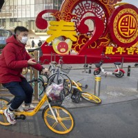 A man wears a face mask as he rides a bicycle past a display for the upcoming Lunar New Year, the Year of the Rat, in Beijing.