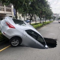 Taiwanese woman injured after road swallows her car